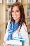 Η γυναίκα σπουδαστής φέρνει τα βιβλία εκπαίδευσης από τη βιβλιοθήκη Στοκ φωτογραφία με δικαίωμα ελεύθερης χρήσης