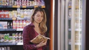 Η γυναίκα στέκεται και παίρνει από το μανιτάρι ψυγείων στην κενή συσκευασία στην υπεραγορά απόθεμα βίντεο