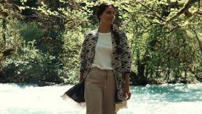 Η γυναίκα στέκεται κοντά στο ρεύμα ενός ποταμού, η κυρία χαίρεται για ένα όμορφο τοπίο απόθεμα βίντεο
