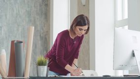 Η γυναίκα στέκεται μπροστά από τον πίνακα, διενεργεί τις προσαρμογές στα σχέδια φιλμ μικρού μήκους
