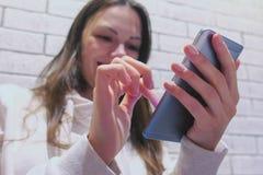 Η γυναίκα στέλνει σε ένα μήνυμα στην κινητές τηλεφωνικές συνεδρίαση και την αναμονή κάποιο στον καφέ στοκ εικόνα με δικαίωμα ελεύθερης χρήσης