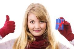 Η γυναίκα στα γάντια που κρατούν το τυλιγμένο δώρο για τα Χριστούγεννα και που παρουσιάζουν φυλλομετρεί επάνω Στοκ φωτογραφίες με δικαίωμα ελεύθερης χρήσης