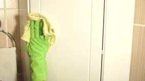 Η γυναίκα στα γάντια πλένει τα έπιπλα λουτρών φιλμ μικρού μήκους