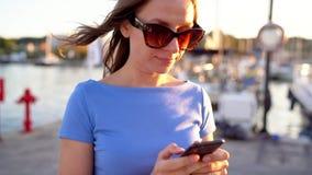 Η γυναίκα στα γυαλιά ηλίου που χρησιμοποιούν το smartphone περπατώντας κάτω από μια αποβάθρα με πολλές γιοτ και βάρκες στο ηλιοβα φιλμ μικρού μήκους