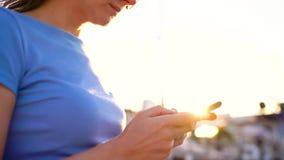 Η γυναίκα στα γυαλιά ηλίου που χρησιμοποιούν το smartphone περπατώντας κάτω από μια αποβάθρα με πολλές γιοτ και βάρκες στο ηλιοβα απόθεμα βίντεο