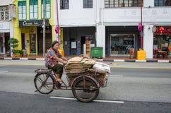 Η γυναίκα στα γυμνά πόδια μετέφερε τα εμπορεύματα με έναν παλαιό, οξύδωσε την τρίκυκλη Σιγκαπούρη Στοκ Εικόνες