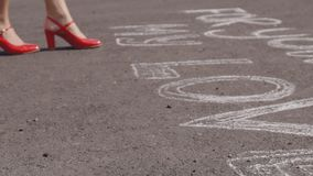 Η γυναίκα στα κόκκινα παπούτσια στην άσφαλτο πρόκειται να αγαπήσει και η ρίψη αυξήθηκε φιλμ μικρού μήκους