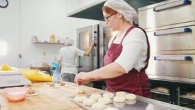 Η γυναίκα στα ποτήρια και την ποδιά ψήνει τα κέικ στο αρτοποιείο φιλμ μικρού μήκους