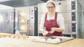 Η γυναίκα στα ποτήρια και την ποδιά ψήνει τα κέικ στο αρτοποιείο απόθεμα βίντεο