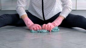 Η γυναίκα στα ρόδινα λαστιχένια γάντια πλένει και τριψίματα σκληρά το λεκέ στο πάτωμα κουζινών με ένα ύφασμα Γκρίζα κεραμίδια στο απόθεμα βίντεο
