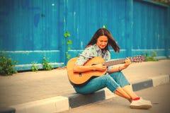 Η γυναίκα στα τζιν κάθεται σε μια οδική συγκράτηση και παίζει την κιθάρα στοκ φωτογραφία