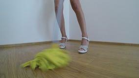 Η γυναίκα στα υψηλά τακούνια πλένει το πάτωμα παρκέ με την κίτρινη σφουγγαρίστρα απόθεμα βίντεο