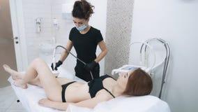 Η γυναίκα στην αρχή του beautician κάνει την αντι διαδικασία cellulite στα πόδια, σε αργή κίνηση φιλμ μικρού μήκους