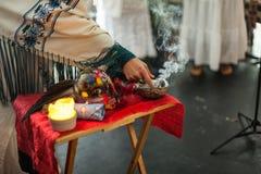 Η γυναίκα στην εθιμοτυπική τήβεννο αγγίζει την καπνίζοντας φασκομηλιά στοκ εικόνες