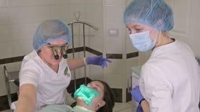 Η γυναίκα στην κλινική οδοντιάτρων παίρνει την οδοντική επεξεργασία για να γεμίσει μια κοιλότητα σε ένα δόντι Οδοντική αποκατάστα απόθεμα βίντεο