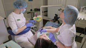 Η γυναίκα στην κλινική οδοντιάτρων παίρνει την οδοντική επεξεργασία για να γεμίσει μια κοιλότητα σε ένα δόντι Οδοντική αποκατάστα φιλμ μικρού μήκους