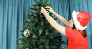 Η γυναίκα στην κόκκινη εξάρτηση Χριστουγέννων διακοσμεί το χριστουγεννιάτικο δέντρο απόθεμα βίντεο