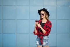 Η γυναίκα στην οδό ενάντια σε έναν μπλε τοίχο μιλά στο τηλέφωνο στοκ εικόνα