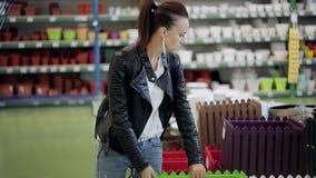 Η γυναίκα στην υπεραγορά επιλέγει το διακοσμητικό δοχείο λουλουδιών Η γυναίκα στο κατάστημα υλικού επιλέγει ένα διακοσμητικό δοχε απόθεμα βίντεο