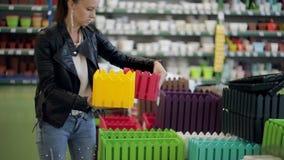Η γυναίκα στην υπεραγορά επιλέγει το διακοσμητικό δοχείο λουλουδιών Η γυναίκα στο κατάστημα υλικού επιλέγει ένα διακοσμητικό δοχε φιλμ μικρού μήκους