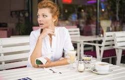 Η γυναίκα στηρίζεται σε έναν καφέ, γυναίκα με μια κούπα, η γυναίκα είναι έκπληκτη Στοκ Εικόνα