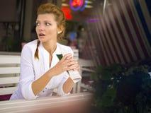 Η γυναίκα στηρίζεται σε έναν καφέ, γυναίκα με μια κούπα, η γυναίκα είναι έκπληκτη Στοκ Φωτογραφίες
