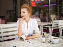 Η γυναίκα στηρίζεται σε έναν καφέ, γυναίκα με μια κούπα, η γυναίκα είναι έκπληκτη Στοκ φωτογραφίες με δικαίωμα ελεύθερης χρήσης