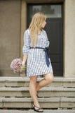 Η γυναίκα στη λαβή φορεμάτων ανθίζει προσιτό Στοκ εικόνες με δικαίωμα ελεύθερης χρήσης