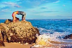 Η γυναίκα στη γιόγκα θέτει στο βράχο παραλιών θάλασσας Στοκ εικόνα με δικαίωμα ελεύθερης χρήσης