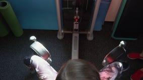 Η γυναίκα στη γυμναστική ταλαντεύεται ένα εσωτερικό μέρος ενός ισχίου Η γυναίκα στα τραίνα περικνημίδων στη γυμναστική φιλμ μικρού μήκους