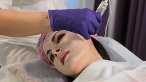 Η γυναίκα στη διαδικασία το δέρμα Το υπομονετικό πρόσωπο ` s στην κινηματογράφηση σε πρώτο πλάνο Η συσκευή φιλμ μικρού μήκους