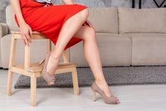 Η γυναίκα στη μοντέρνη κοντή φούστα φορεμάτων υψηλή βάζει τακούνια στο κάθισμα σε ένα ξύλινο σκαμνί κοντά στον καναπέ στοκ φωτογραφίες
