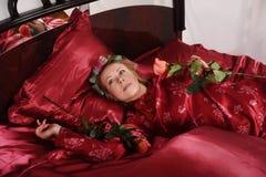 Η γυναίκα στις κόκκινες πυτζάμες που βρίσκονται σε ένα κρεβάτι στο κόκκινο λινό μεταξιού με τα ρόλερ τρίχας και αυξήθηκε στο χέρι στοκ εικόνες