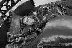 Η γυναίκα στις κόκκινες πυτζάμες που βρίσκονται σε ένα κρεβάτι στο κόκκινο λινό μεταξιού με τα ρόλερ τρίχας και αυξήθηκε στο χέρι στοκ φωτογραφία με δικαίωμα ελεύθερης χρήσης