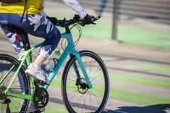 Η γυναίκα στις περικνημίδες και τα πάνινα παπούτσια παρακολουθεί της μορφής και του βάρους της και οδηγά το ποδήλατο στοκ εικόνες