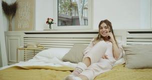 Η γυναίκα στις πυτζάμες πρέπει να χαλαρώσει το χρόνο στο άνετο κρεβάτι της μιλώντας στο τηλέφωνο και να έχει μια καλή διάθεση απόθεμα βίντεο