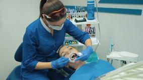 Η γυναίκα στον οδοντίατρο μεταχειρίζεται τα δόντια απόθεμα βίντεο