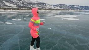 Η γυναίκα στον πάγο το χειμώνα είναι κάνει τον αθλητισμό στο αθλητικό περπάτημα φυλών Το κορίτσι εκπαιδεύει το χειμώνα στον πάγο  φιλμ μικρού μήκους