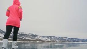 Η γυναίκα στον πάγο το χειμώνα είναι κάνει τον αθλητισμό στο αθλητικό περπάτημα φυλών Το κορίτσι εκπαιδεύει το χειμώνα στον πάγο  απόθεμα βίντεο