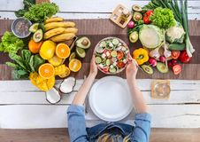 Η γυναίκα στον πίνακα γευμάτων με τη οργανική τροφή, η άποψη από την κορυφή στοκ φωτογραφία με δικαίωμα ελεύθερης χρήσης