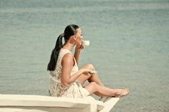 Η γυναίκα στον ωκεανό πίνει τον καφέ Θάλασσα ή ωκεάνια και πίνοντας γυναίκα Στοκ Φωτογραφία