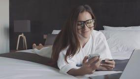 Η γυναίκα στο άσπρο μπουρνούζι και τα γυαλιά που ψωνίζουν on-line με την πιστωτική κάρτα και το smartphone, βρίσκονται στο κρεβάτ απόθεμα βίντεο