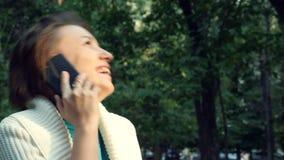 Η γυναίκα στο άσπρο πουκάμισο κάθεται στον πάγκο μιλά το smartphone κυττάρων γελώντας στο ηλιοβασίλεμα φιλμ μικρού μήκους
