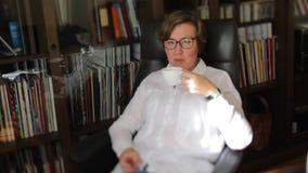 Η γυναίκα στο άσπρο πουκάμισο παίρνει τον καφέ, ποτά, χαμόγελα απόθεμα βίντεο