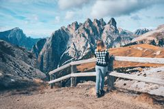 Η γυναίκα στο ίχνος εξετάζει στα μεγαλοπρεπή βουνά το ηλιοβασίλεμα στοκ φωτογραφία