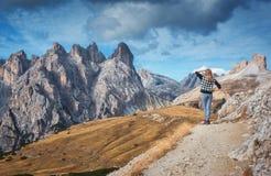 Η γυναίκα στο ίχνος εξετάζει στα μεγαλοπρεπή βουνά το ηλιοβασίλεμα στοκ εικόνα