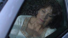 Η γυναίκα στο αυτοκίνητο εξετάζει τη βροχή απόθεμα βίντεο