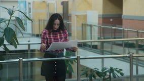 Η γυναίκα στο γραφείο κοιτάζει στο στρέθιμο της προσοχής στα μεγάλα φύλλα του εγγράφου απόθεμα βίντεο