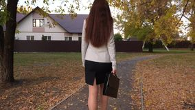 Η γυναίκα στο επιχειρησιακό κοστούμι με το μαύρο χαρτοφύλακα στο χέρι της περπατά κατά μήκος της πορείας μέσω του πάρκου πόλεων υ φιλμ μικρού μήκους