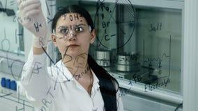 Η γυναίκα στο εργαστήριο γράφει τον τύπο στον πίνακα γυαλιού απόθεμα βίντεο